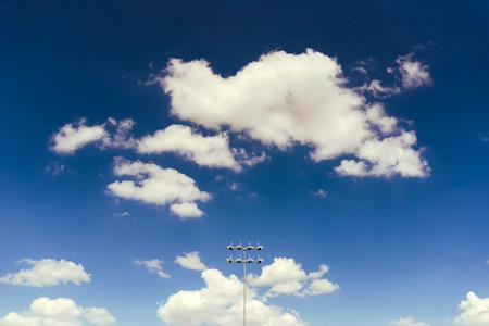 Stadium lights against blue sky with white clodus, minimalistic composition Stock Photo