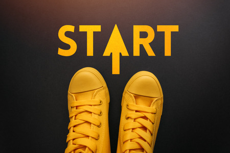 Standing at the Start line conceptual image with person in yellow sneakers, top view