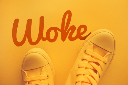 Words and phrases millennials use, conceptual image with young person in yellow sneakers standing directly above text - Woke Stock Photo