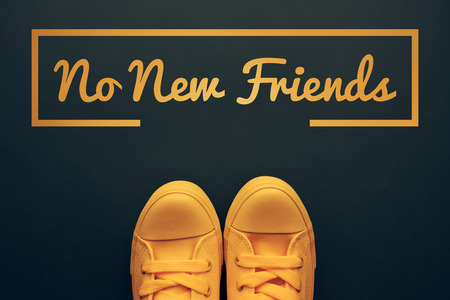 Words and phrases millennials use, conceptual image with young person in yellow sneakers standing directly above text - No new friends Stock Photo