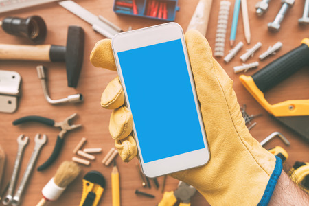 Handyman smart phone app over desk with tools. Repairman holding telephone in hand. Copy space for text, top view Stock Photo