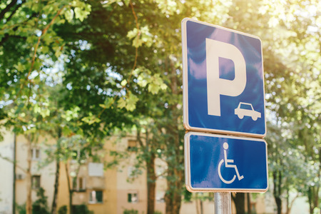 Disabled person parking spot sign, reserved lot space for handicapped person, selective focus