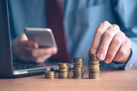 Businessman using smartphone with stacked coins in foreground, close up shot with selective focus