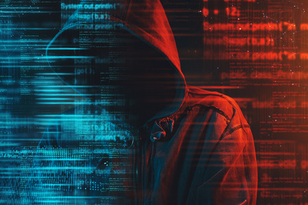 Stereotypical image of computer hacker with hoodie and computer code. Faceless hooded male person lit with red and blue light, conceptual low key image.