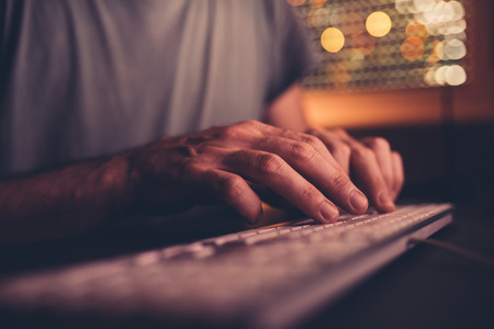 Hands type computer keyboard. Man using desktop pc in home office low light interior, selective focus Stock Photo