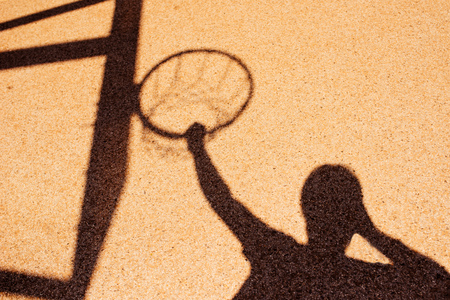 Shadow of male basketball player in slam dunk pose, holding the hoops