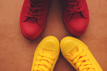 Young couple on a love date, conceptual image. Top view of two pair of casual sneakers, yellow and red, from above close to and facing each other like when people are intimate and kissing. Stock Photo
