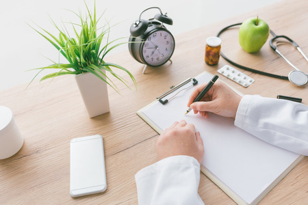 Female doctor writing notes, patients medical history or medicine prescription on clipboard paper during medical exam in hospital office Stock Photo