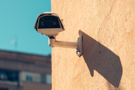 Private property protection security camera mounted on house exterior wall