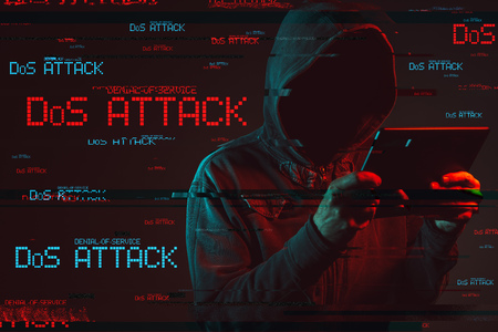 Denial of service or DDoS attack concept with faceless hooded male person using tablet computer, low key red and blue lit image and digital glitch effect