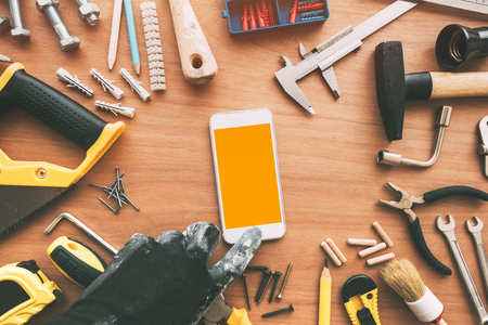 Handyperson smart phone app with blank screen. Repairman holding mobile phone in hand. Copy space for maintenance work application or business service message, top view Stock Photo