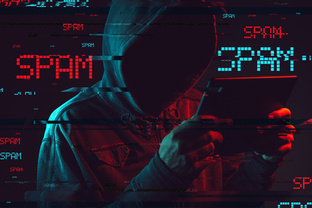 Electronic spamming  concept with faceless hooded male person using tablet computer, low key red and blue lit image and digital glitch effect