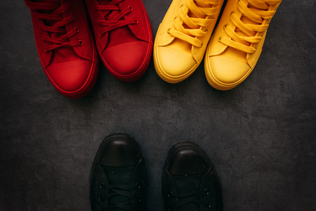 Youth confrontation conceptual image. Young people in colorful sneakers confronting a person in black casual shoes.
