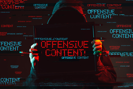 Offensive content concept with faceless hooded male person holding computer monitor, low key red and blue lit image and digital glitch effect