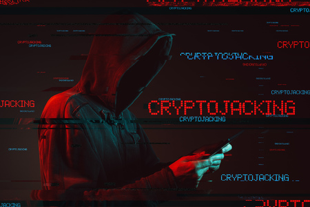 Cryptojacking scam concept with faceless hooded male person using tablet computer, low key red and blue lit image and digital glitch effect