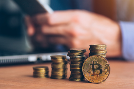 Bitcoin cryptocurrency trader, business person using modern technology electronic to trade with crypto money, stacked coins in the foreground and defocussed businessman in background
