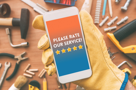 Please rate our service message on smartphone screen in male hand. Customer service survey feedback concept.