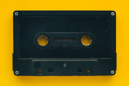 Audio cassette tape on yellow background, retro vintage technology Stock Photo