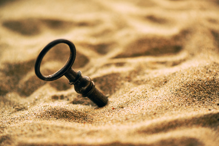 Old lost key in the sand is a newly found opportunity