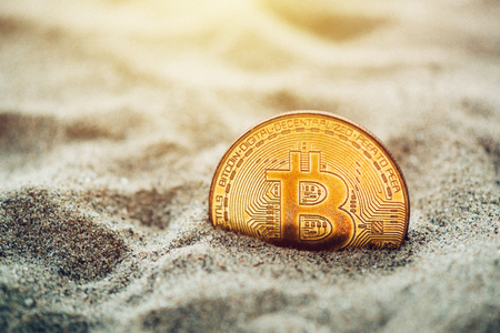 Single bitcoin cryptocurrency coin buried in sand, conceptual image for crypto mining and newly found treasures metaphor, selective focus