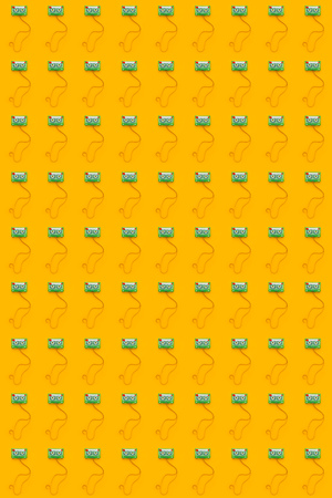 Seamless pattern background of audio cassettes with tangled tape on bright yellow backdrop, minimalistic top view composition Stock Photo