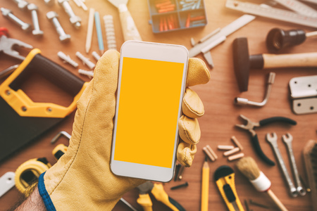 Flatlay maintenance handyman smartphone app with blank screen. Repairman holding device in hand. Archivio Fotografico