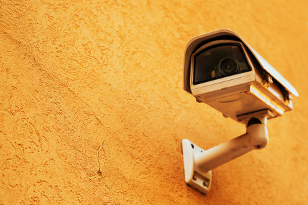 Private property protection concept with outdoor security camera in metal housing mounted on exterior wall