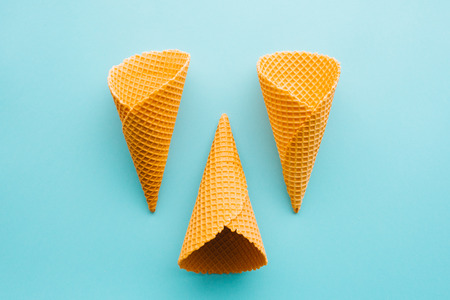 Three ice cream cones from above on pastel blue background, minimal flat lay composition with copy space
