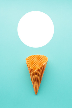 Ice cream cone from above on pastel blue, minimal flat lay composition with copy space Stock Photo