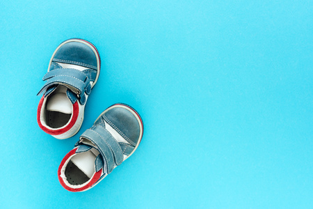Top view of newborn baby boy shoes on blue background with copy space