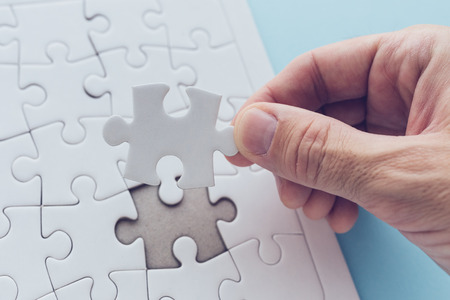 Man successfully solving jigsaw puzzle, hand putting a missing piece to complete the solution Stock Photo