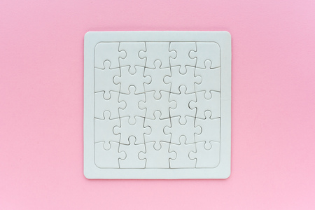 Complete blank jigsaw puzzle as mock up copy space, top view of surface on pink background