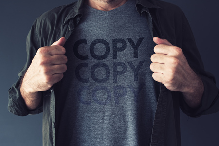 Copycat and plagiarism concept, repeating word Copy is fading on guy's t-shirt Archivio Fotografico