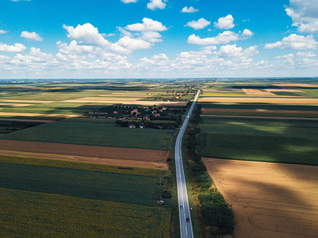 Aerial view of road through countryside landscape on sunny summer day