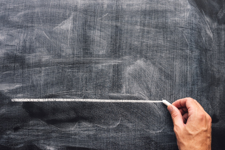 Hand underlining with chalk on school blackboard. Teacher emphasizing something important, mock up copy space Stock Photo