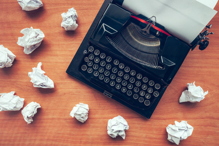 Writers block concept with typewriter and crumpled paper on work desk Stock Photo