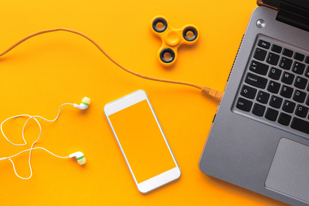 Gadgets belonging to young person - laptop and smart phone with earphones and fidget spinner in top view flat lay style Stock Photo