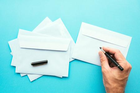 Hand writing address on blank white envelope, mock up image for communication and correspondence themes Stock Photo