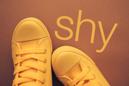 Shy person and shyness, conceptual image with yellow sneakers from above