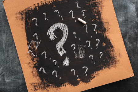 Sketched question marks on cardboard paper, concept of perplex and confusion