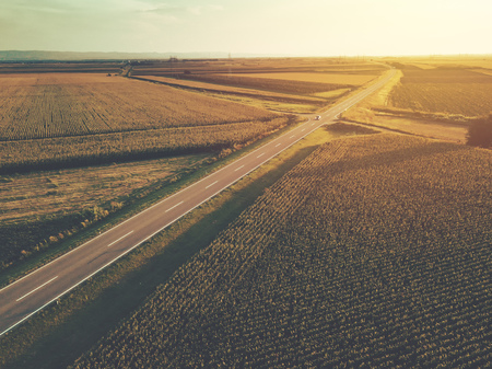 Aerial view of two-lane freeway road through countryside and cultivated field of corn in summer sunset, retro toned