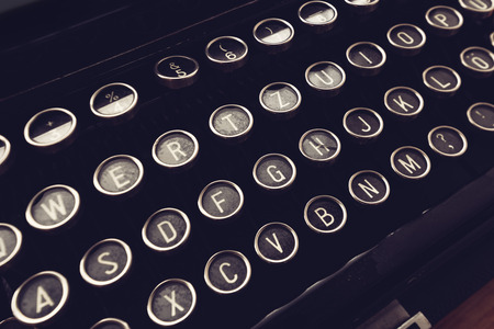 Close up of vintage typewriter machine keys on writers desk, conceptual image for blogging, publishing, journalism or poetry writing.
