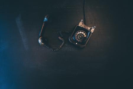 Black vintage landline telephone, old and weathered. Broken communication concept. Фото со стока