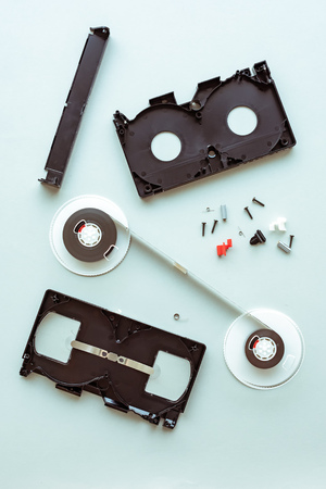 Flat lay vhs video cassette parts on pastel blue background, top view of retro technology and media concept