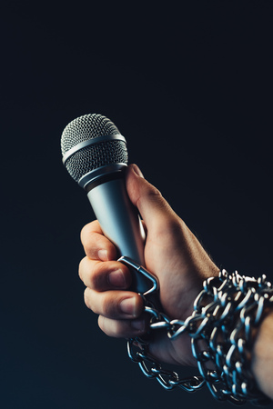 Freedom of the press and journalism, conceptual image with microphone in male hand tied with chains, low key image