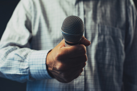 Hand with microphone doing an interview for the media, selective focus