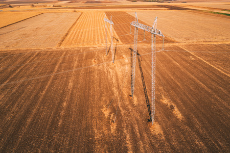 High voltage electricity pylons for power transmission in field from drone pov