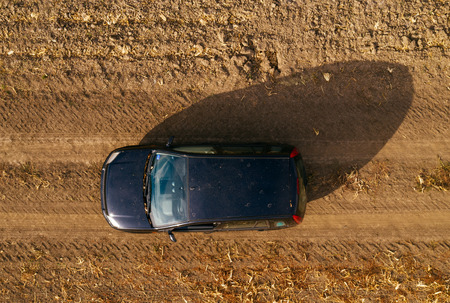 Aerial view of black car on dirt road through countryside, top view of off-road driving vehicle from drone pov Stok Fotoğraf