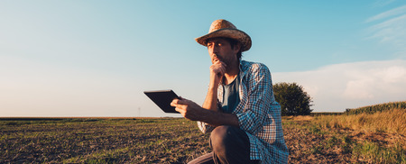 Farmer agronomist with tablet computer in bare empty field in sunset, serious confident man using modern technology in agricultural production planning and preparation Stock fotó