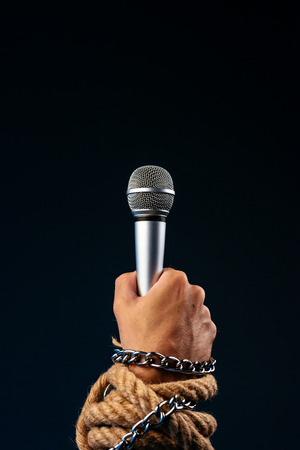 Freedom of the press and journalism, conceptual image with microphone in male hand tied with chains and ropes, low key image
